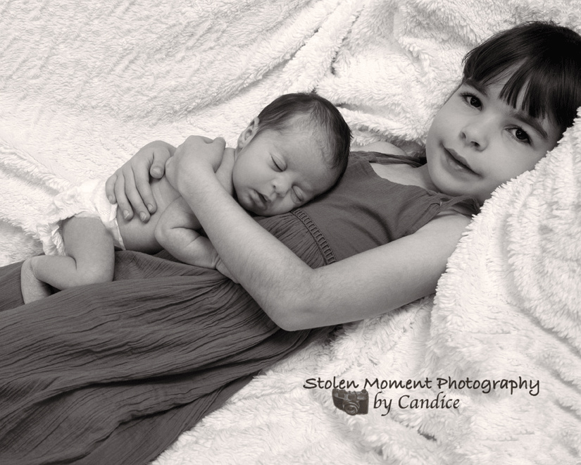 Older sister holding her newborn sister while she sleeps