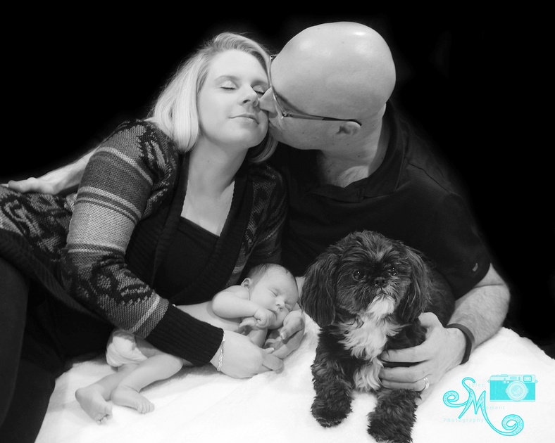 a new dad leans over and kisses his wife while their newborn lays beside them next to their puppy