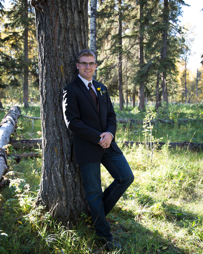 groom striking a pose against a tree