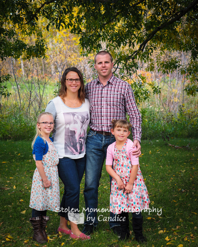 Family of four in front of beautiful fall trees