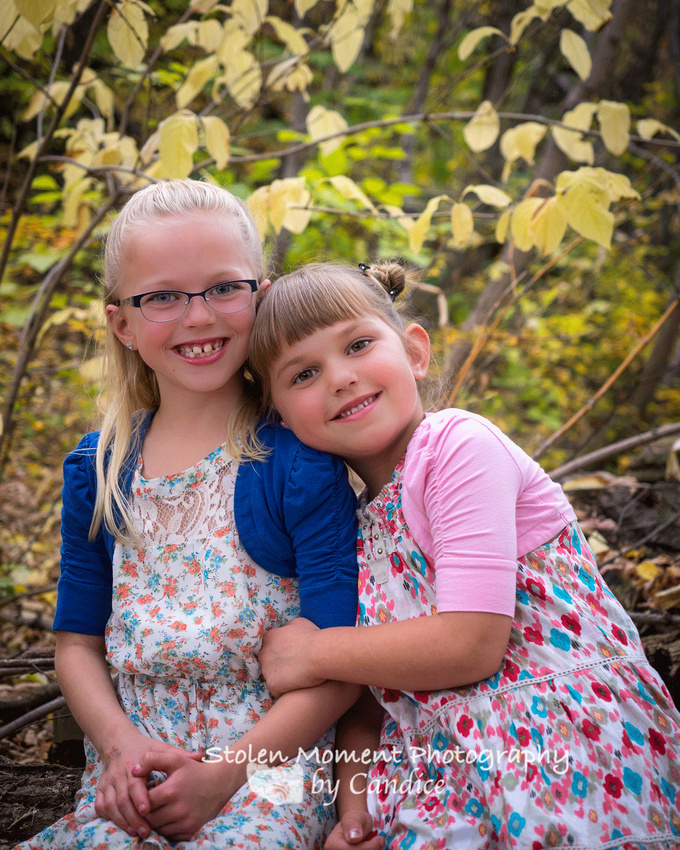Two sweet sisters cuddling in front of fall trees