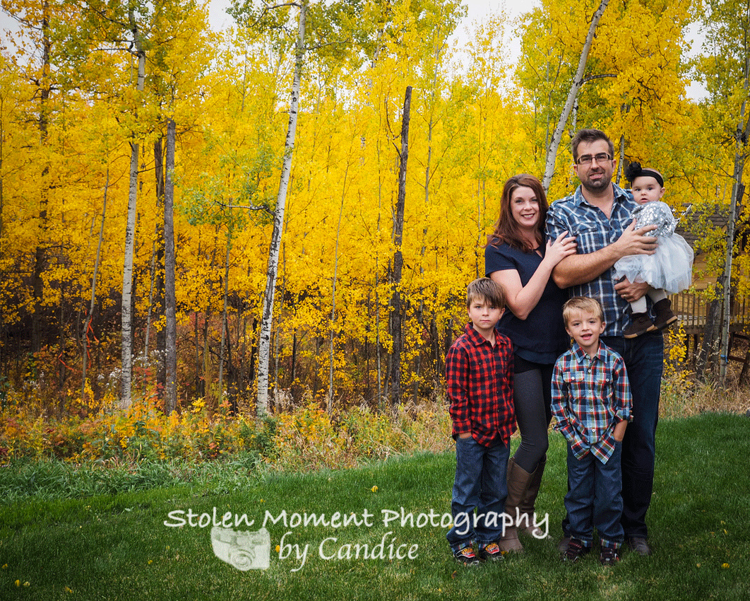Family of five standing in front of gorgeous fall foilage