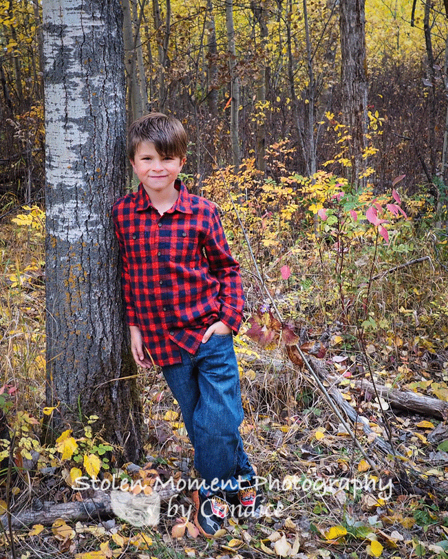 young boy leaning on tree in the fall