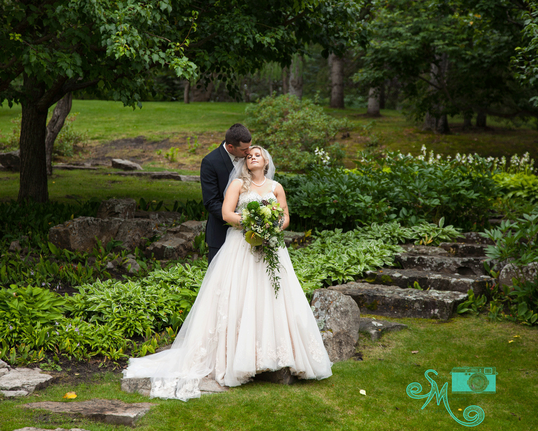 Groom kissing bride's forehead in a beautiful wooded area