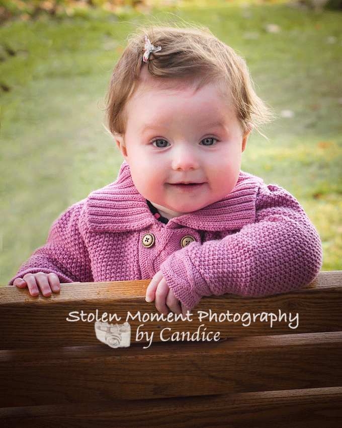 baby looking over back of bench with big smile