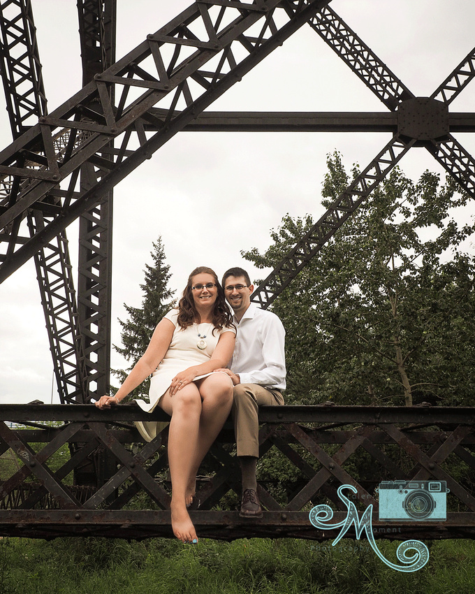 man and woman sitting on structure of a bridge