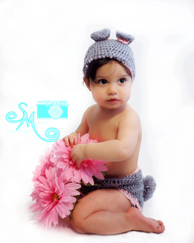 little girl in bunny ears and bottom holding pink flowers