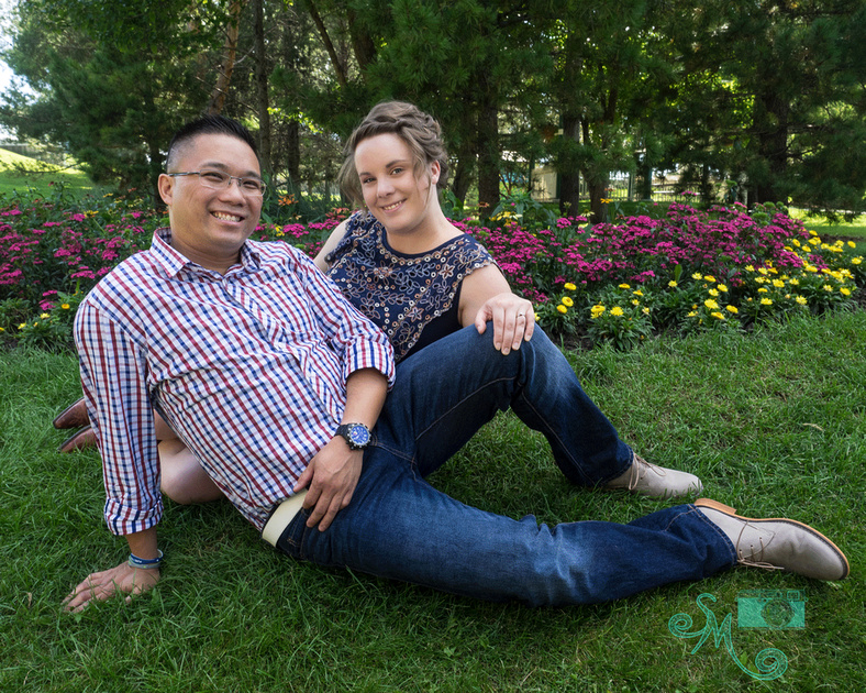 couple sitting on the ground in front of flowers