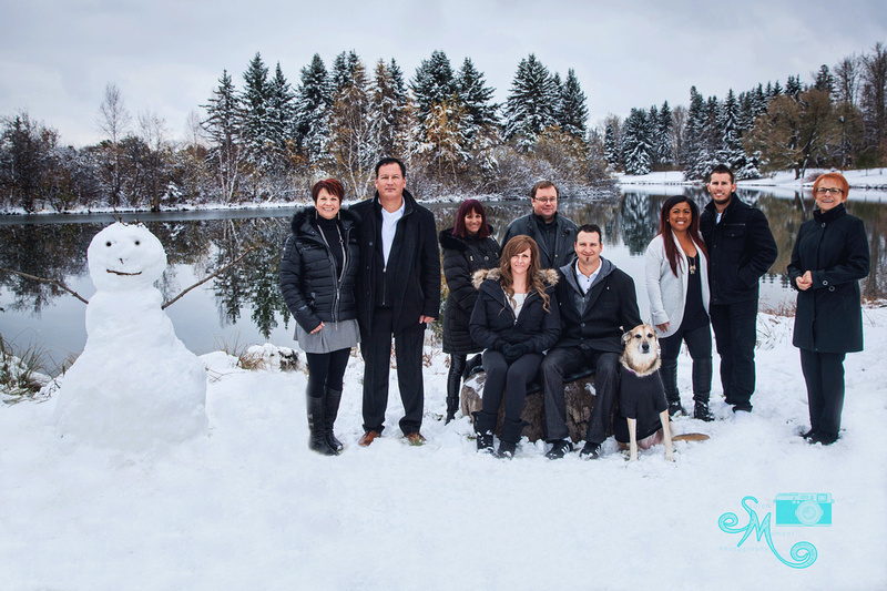 a family of eight stands in front of a lake with a snowman beside them
