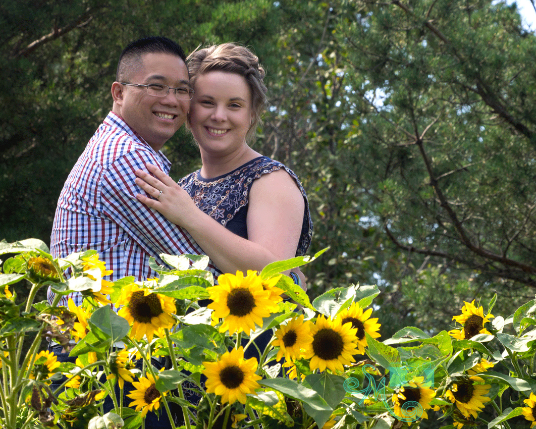 couple embracing behind some sunflowers