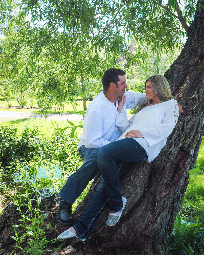 Man looking into his fiance's eyes as she leans against tree