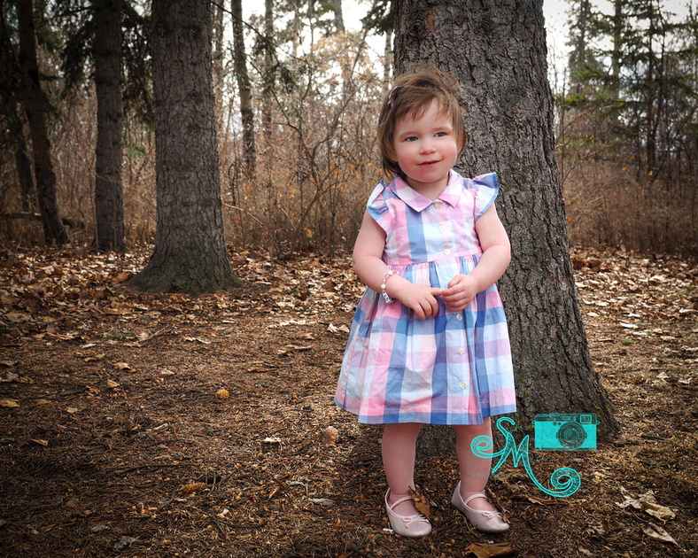little girl standing by tree
