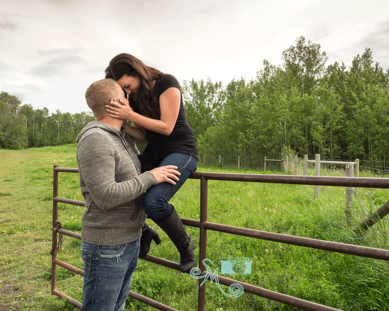 couple snuggling while woman sits on gate