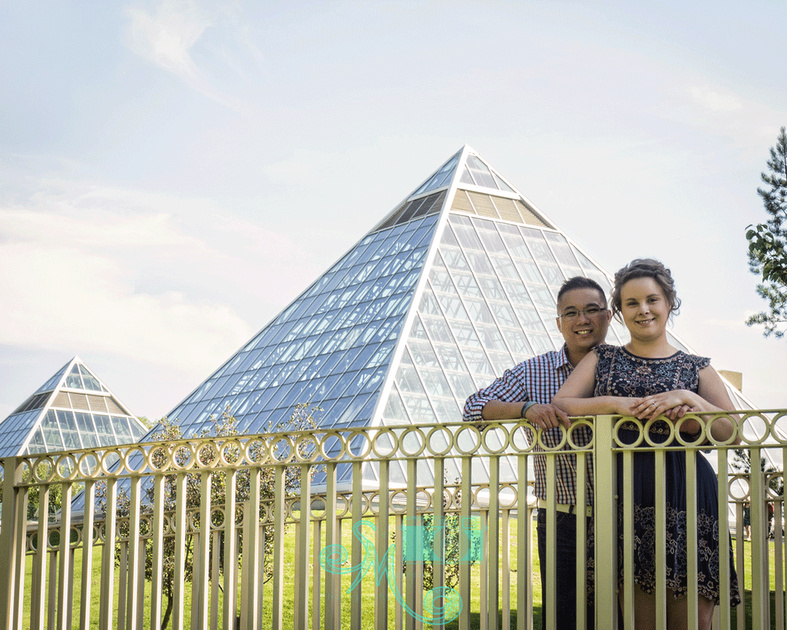 Couple posing on bridge with pyramids of the Muttart Conservatory in the background