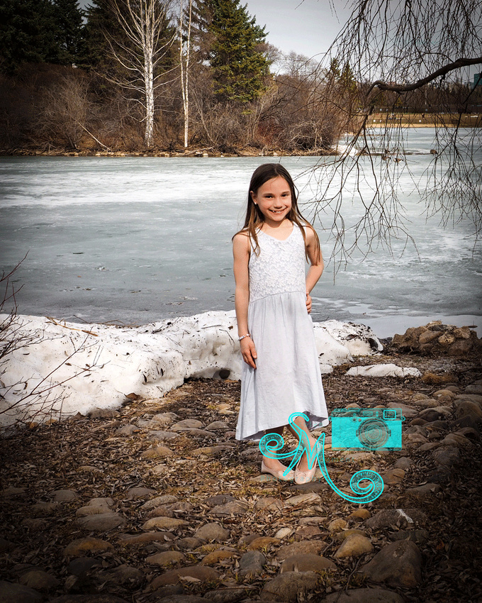 little girl standing in front of lake