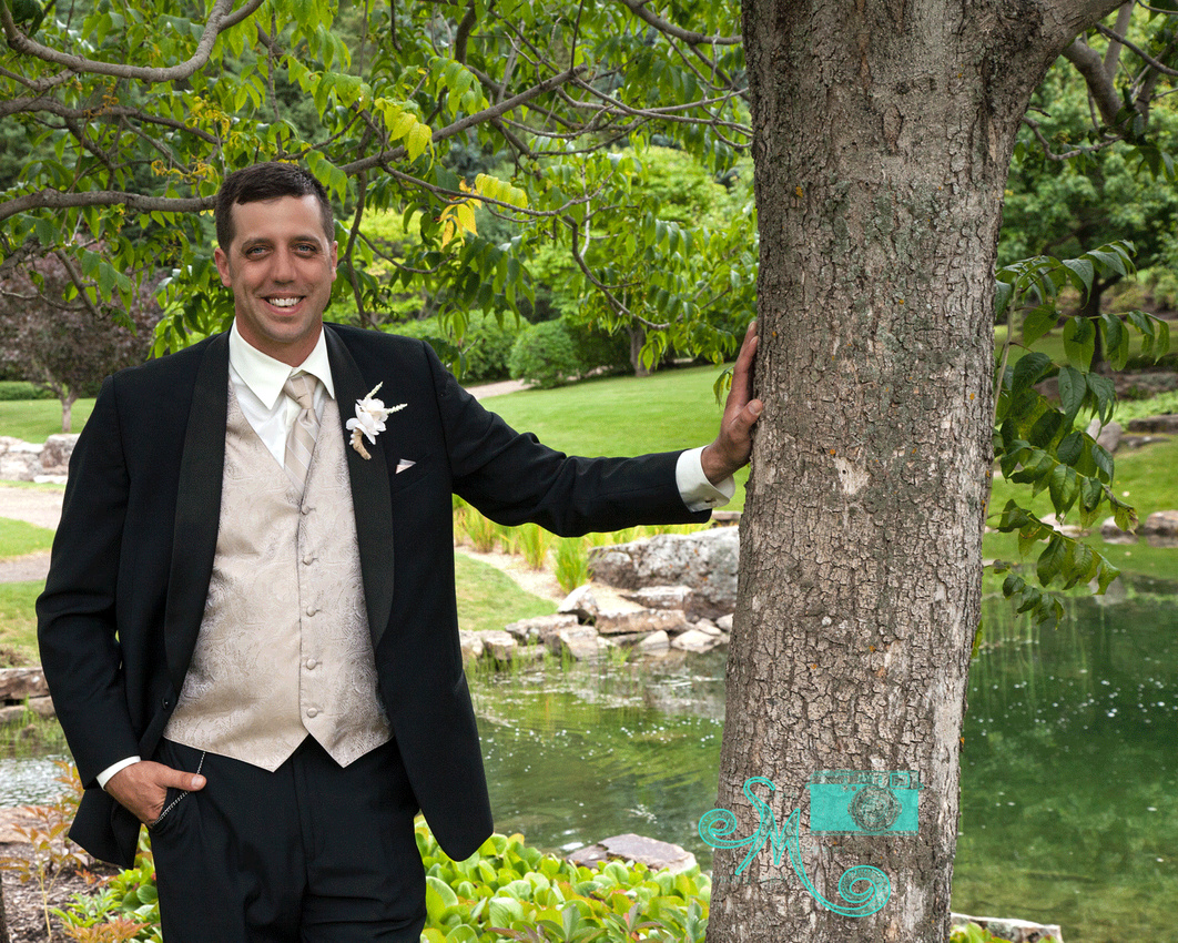 Groom standing with hand on tree with pond in background