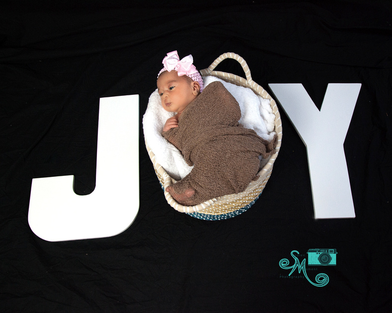 "Newborn girl in basket becomes letter ""o"" in the word ""JOY"""