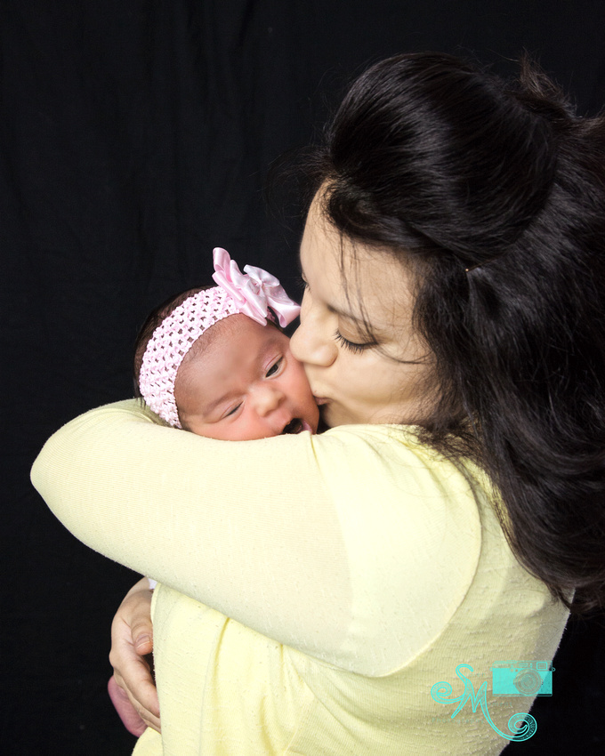 Mom gives her newborn daughter a kiss