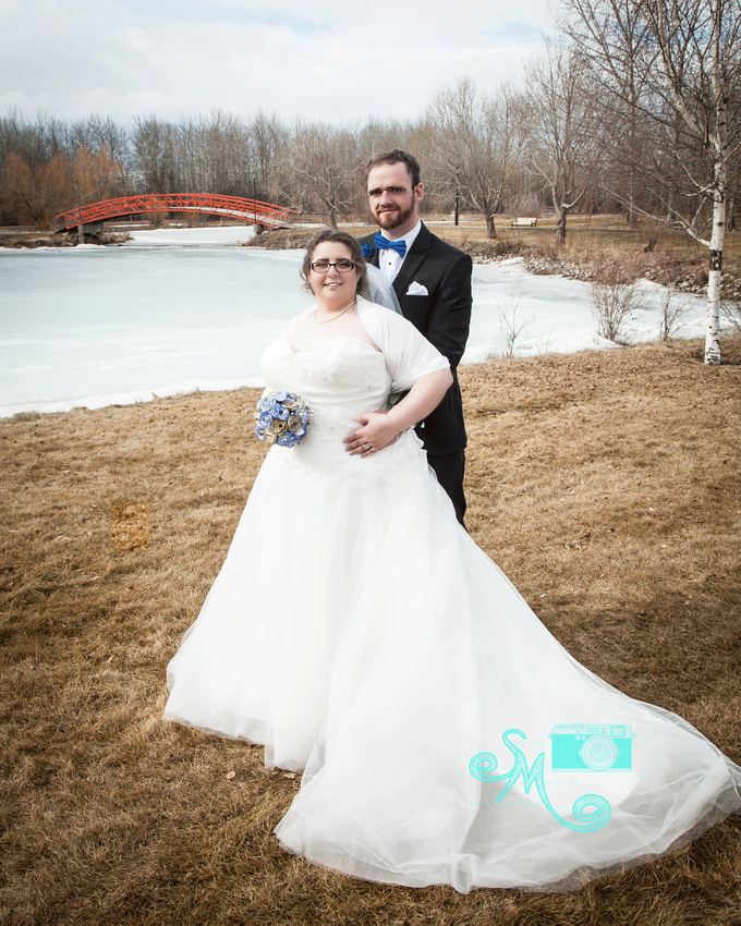 bride and groom pose for formal photo at dog rump creek park with bridge and lake in background