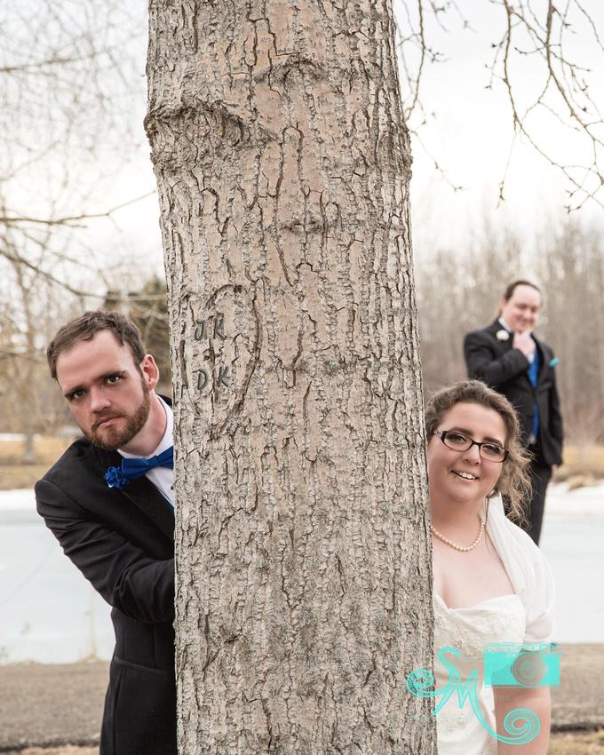 bride and groom peeking around a tree while a groomsmen looks on