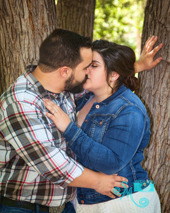 Man kisses his fiance while leaning into a tree