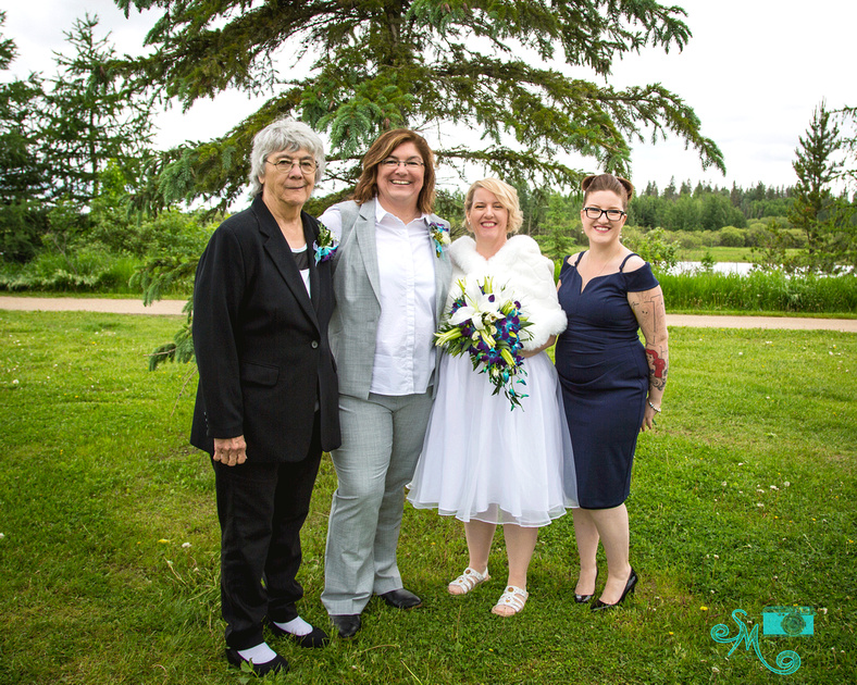 a bride and her mom and the other bride and her daughter pose for a photo