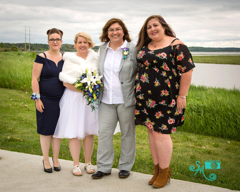 the brides and their witnesses pose for a photo in front of a lake