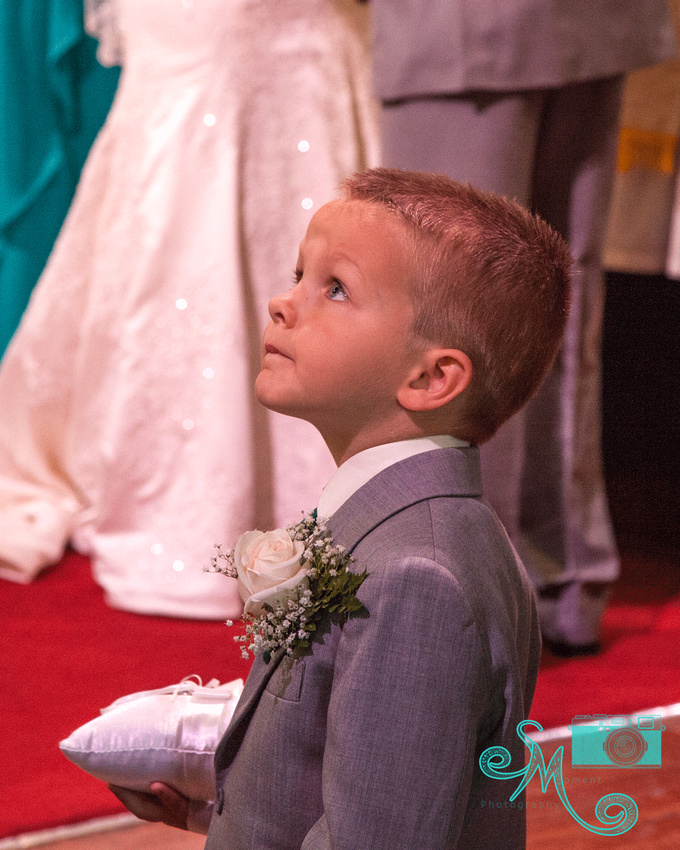 the ring bearer looks upward during the ceremony