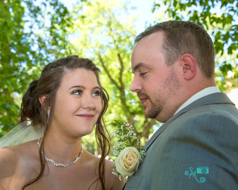 a bride and groom share a quick look between photos