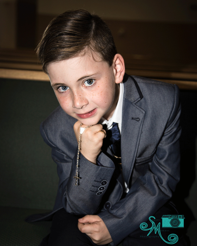 a boy looks into the camera while resting his arm on his leg and holding his rosary