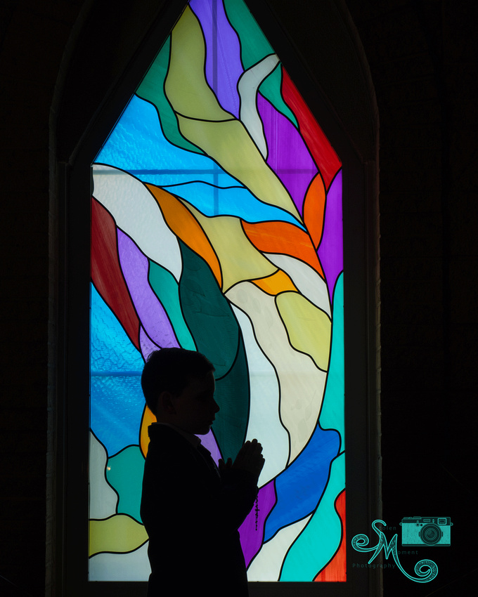 a boy in silhouette with hands clasped in prayer in front of a stained glass window