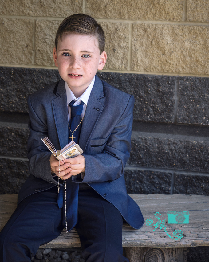 a boy sits on a bench holding his rosary