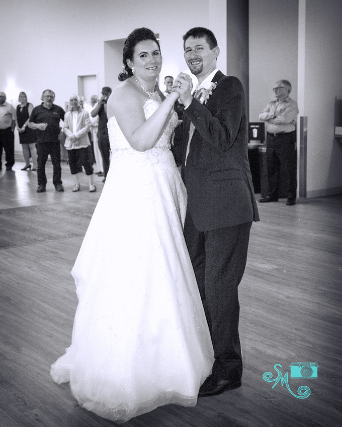 bride and groom smile for a photo during the first dance