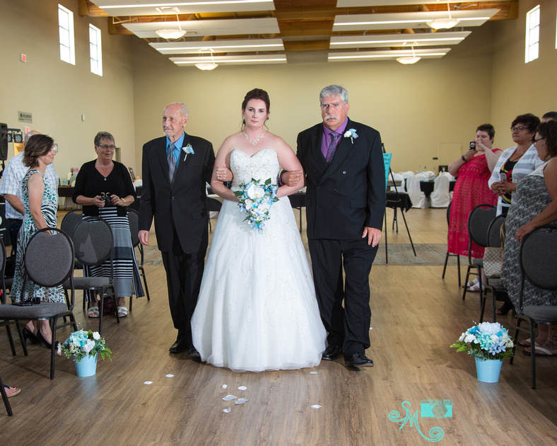 bride being walked down the aisle by her father and stepfather