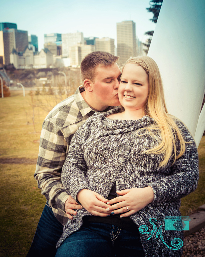 a man kisses his fiance's cheek with downtown Edmonton in the background