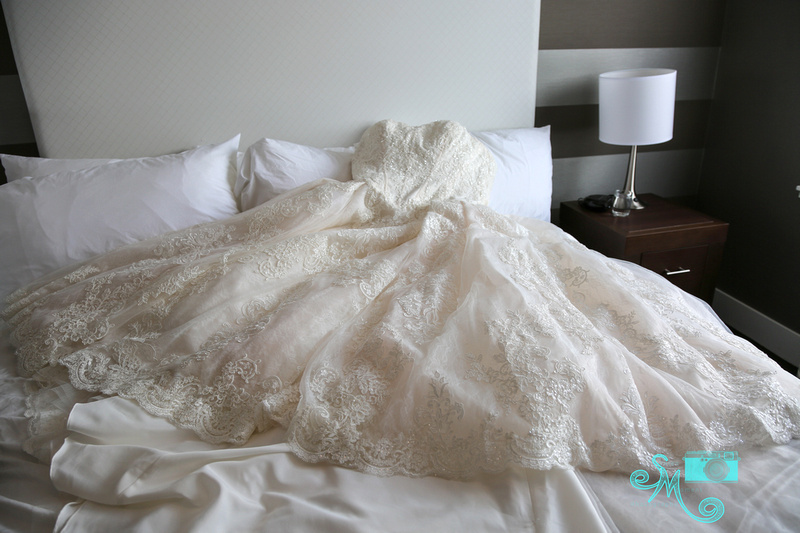 the bride's dress lays on a bed
