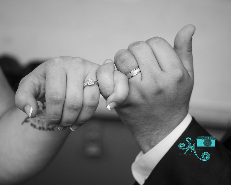 the bride and grooms hands in a pinky swear showing off the rings