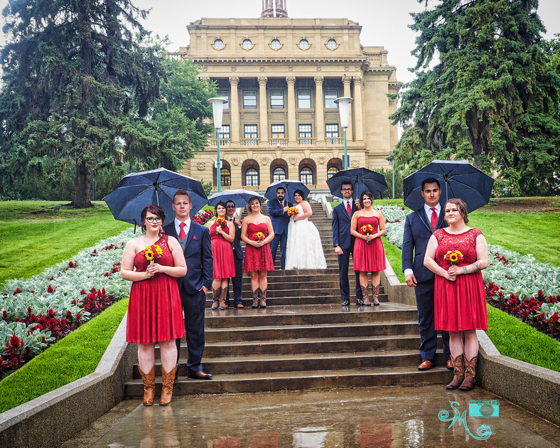 the entire wedding party uses umbrellas and stand in the rain on the steps on the grounds of the Alberta Legislature