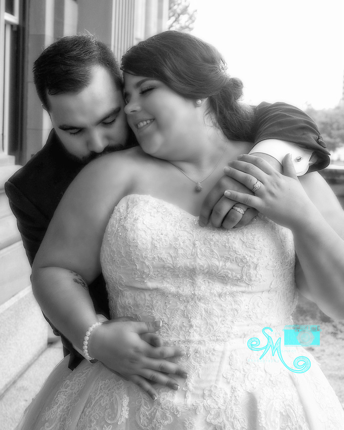 the grooms holds his bride and kisses her shoulder