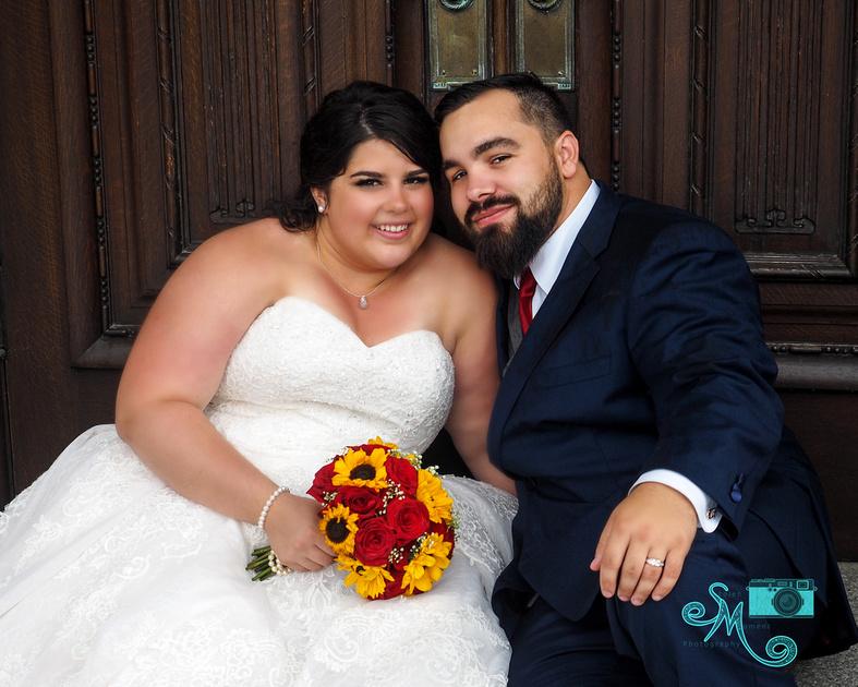 the bride and groom sit in front of the door of the legislative building