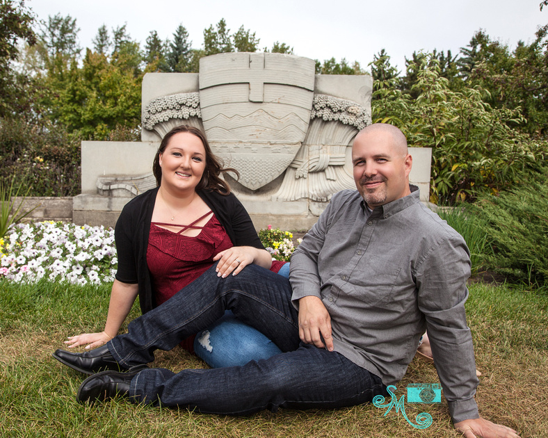 a man and his fiance sit in front of an Alberta coat of arms statute