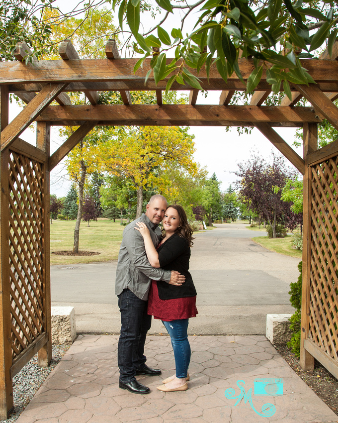 A man and woman embrace under an arbour