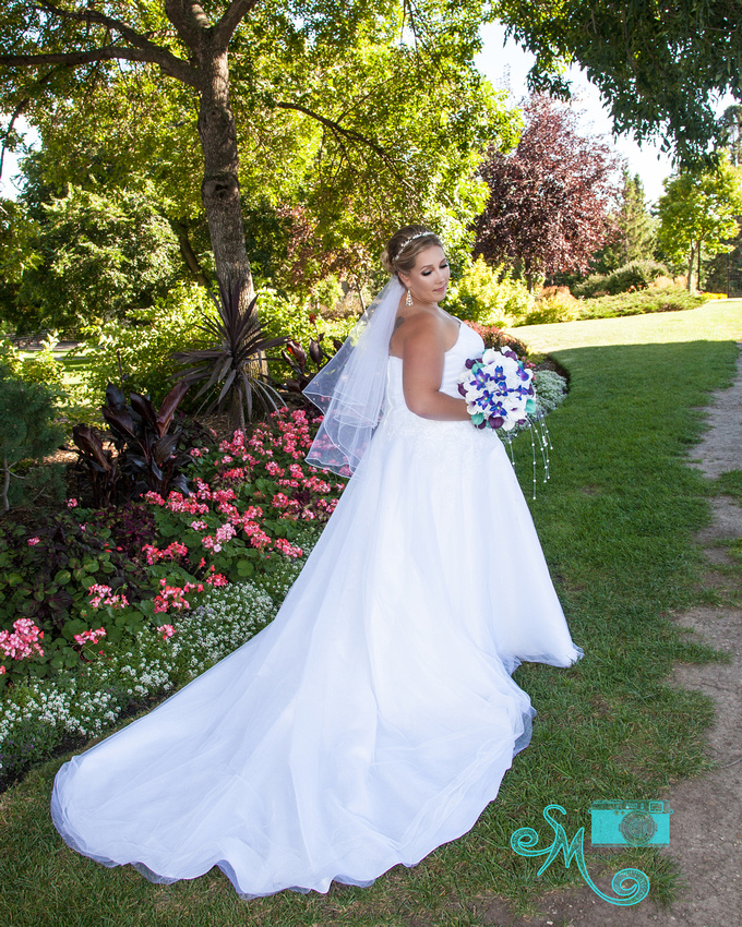 a beautiful bride poses in front of pink flowers