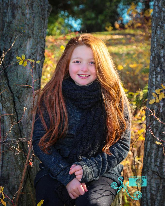 girl sits on a tree stump amongst the fall leaves at Hawrelak park