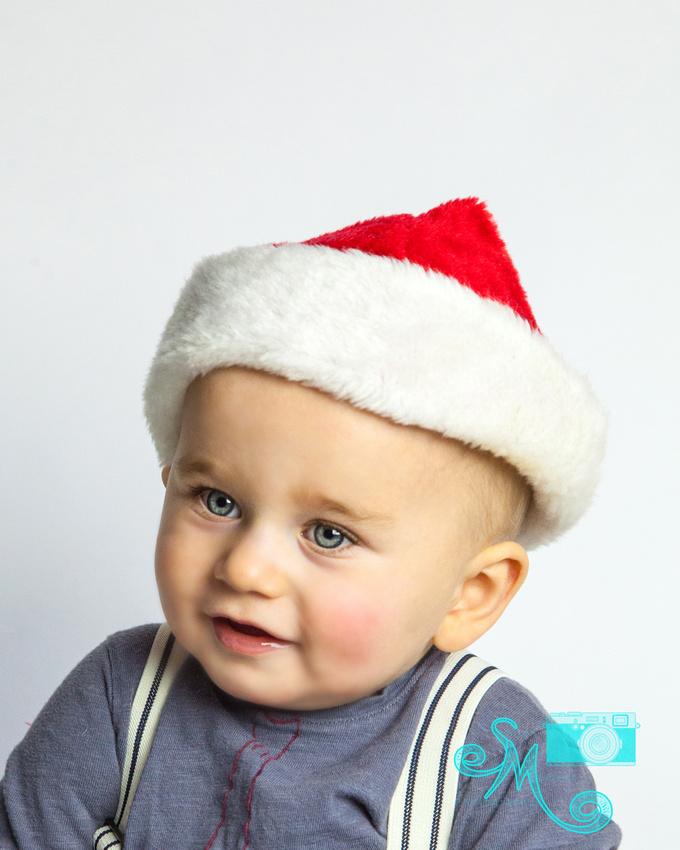 a little boy in Santa hat smiles