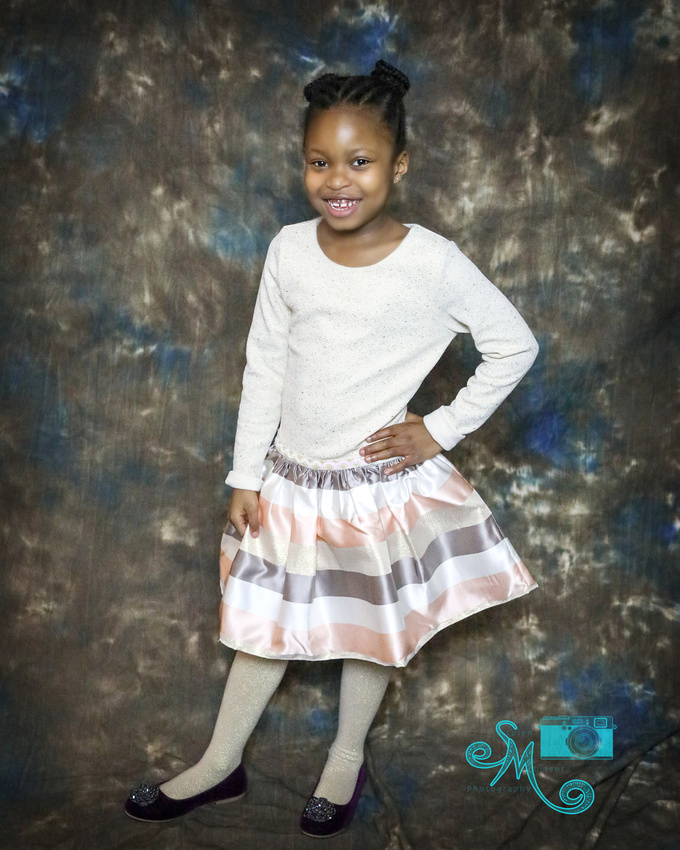 a little girl stands hand on hip posing in studio