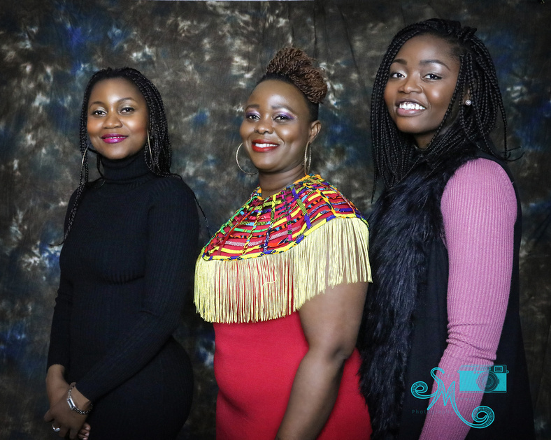 Two sisters and sister in law stand posing for camera in studio