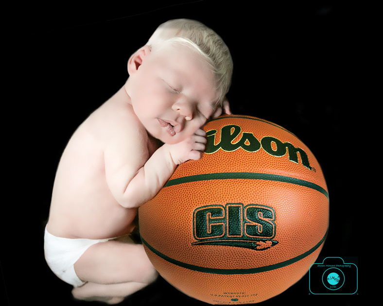 a seven day baby boy sleeps on a basketball