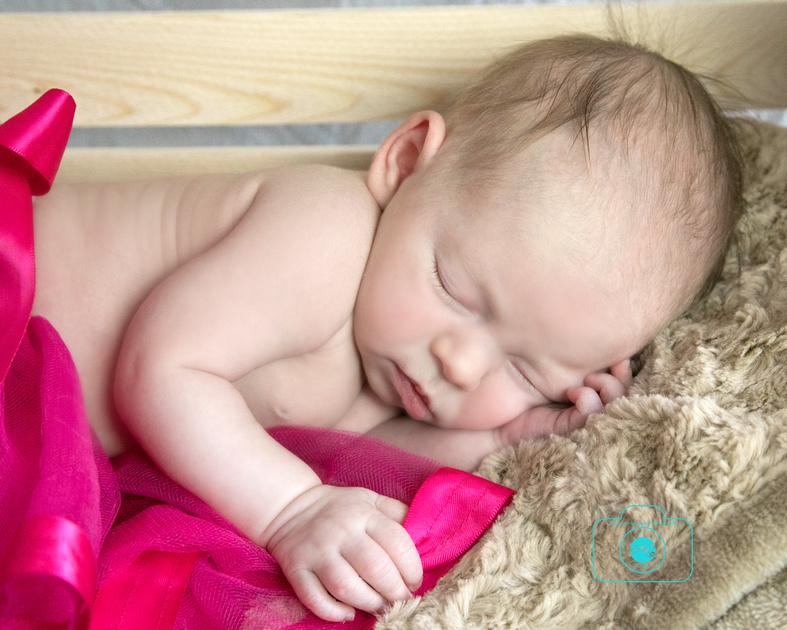 sweet little newborn girl lays on her side sleeping