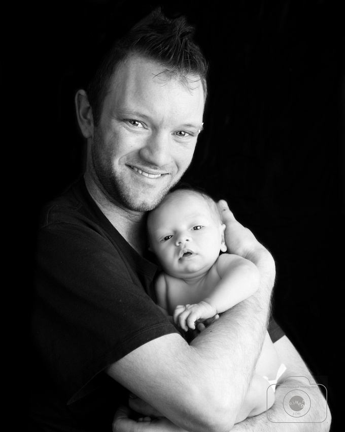 dad cradles his newborn daughter in his arms while smiling proudly into camera